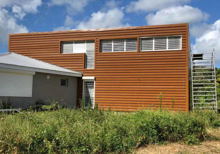 Maison avec un bardage en tôle Guadaba imitation chêne clair par TPG, Tropic Profil Guadeloupe