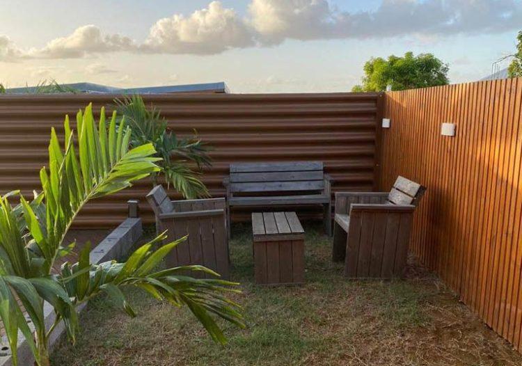 Bardage Ondulea imitation bois chêne clair autour d'un salon de jardin, par TPG, Tropic Profil Guadeloupe